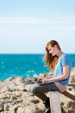 Woman working on her laptop at the seaside sitting on a wooden railing overlooking a rocky shoreline and the ocean photo