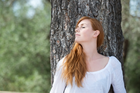 closed up: Beautiful woman relaxing in woodland standing leaning against the trunk if a tree with her eyes closed in enjoyment and bliss