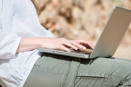 Closeup view of the hands of a young woman typing on her laptop sitting outdoors in sunshine photo