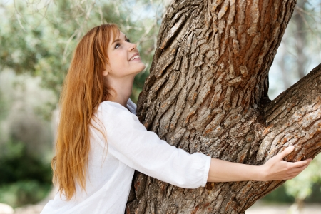 looking around: Nature lover concept with a beautiful young girl standing embracing a tree trunk with a smile of pleasure