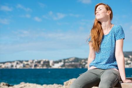 ojos cerrados: Mujer bonita disfrutando del sol mientras estaba sentado en una barandilla de madera en la costa con vistas al mar