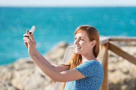 Pretty young woman photographing herself with a mobile phone at the seaside photo