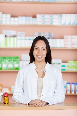 smiling young employee standing behind pharmacies counter photo