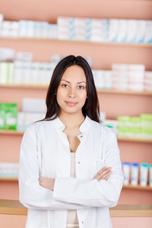 young saleswoman with folded arms working in a drug store photo