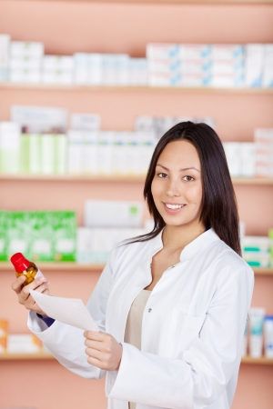 young woman standing against shelves in pharmacy photo