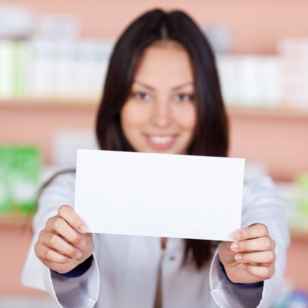 asian pharmacist displaying white paper in pharmacy photo