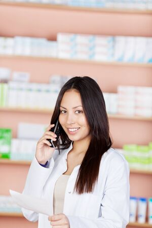 woman using phone in pharmacy and holding prescription paper photo