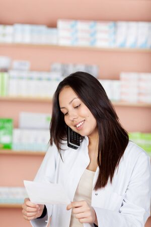 pharmacist using phone and holding prescription in hands photo