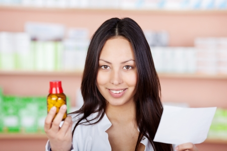young pharmacist holding medicine and prescription in hands photo