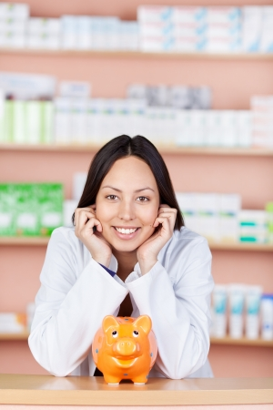 young saleswoman in drug store with piggy bank leaning head on photo