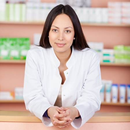 portrait of a smiling female pharmacist leaning on counter photo