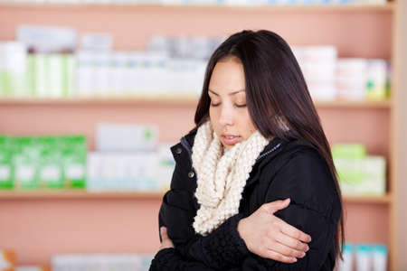 young asian woman suffering from cold standing in a drug store photo
