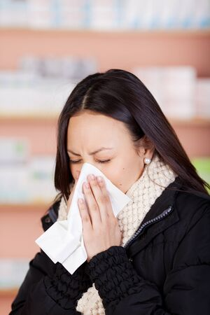 young woman with a cold using paper tissue in pharmacy photo