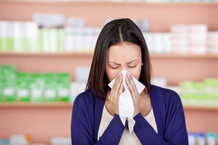 young woman with a cold using tissue in pharmacy photo