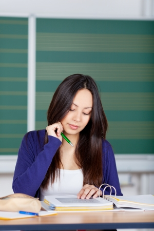 concentrated: asian girl sitting in class room and reading in binder concentrated Stock Photo