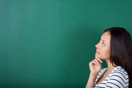 asian teacher: young woman thinking about something looking on blackboard Stock Photo