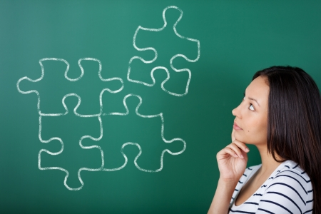 young woman in school completing puzzle on blackboard photo