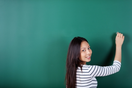smiling student writing on empty blackboard looking back over shoulder photo