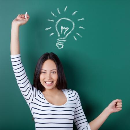 happy woman in school with light bulb drawn on blackboard photo