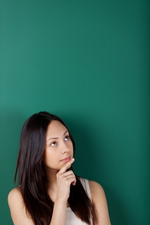 portrait of a pensive young woman against blackboard photo