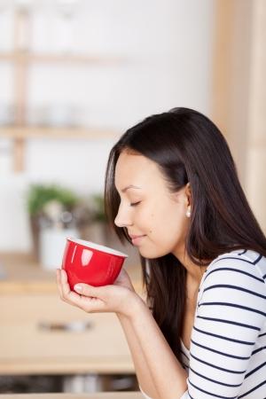 olfato: Mujer disfrutando del aroma de café en casa con los ojos cerrados