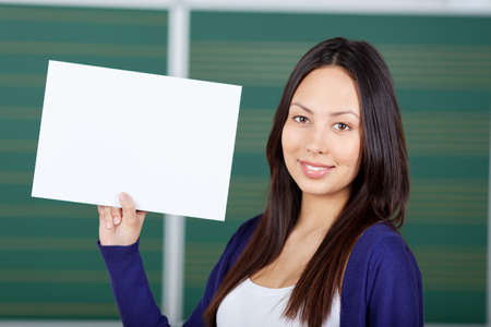 uni: female student displaying white paper in classroom