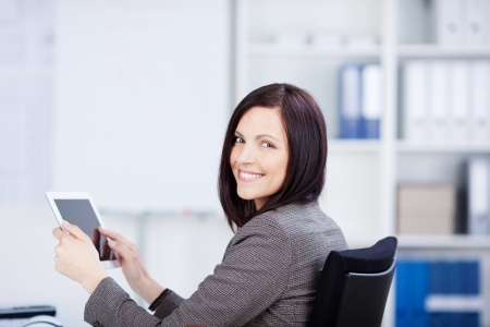 Smiling businesswoman working and holding a tablet photo