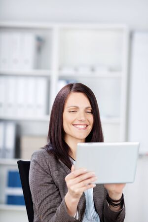 Smiling woman sitting in a chair in an office reading from the screen of a laptop computer photo