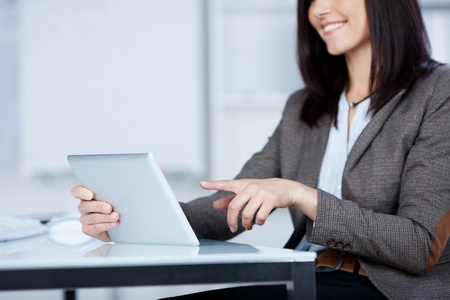 handholding: Smiling woman sitting at a desk pointing to the screen of her tablet computer which she is handholding