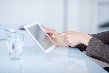 Hands of a woman pointing to a blank angled tablet computer screen as she sits at a white desk photo