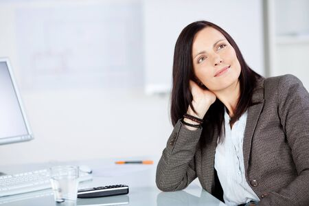 Portrait of businesswoman daydreaming inside the office photo