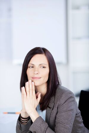 Businesswoman sitting in the office while looking at something photo