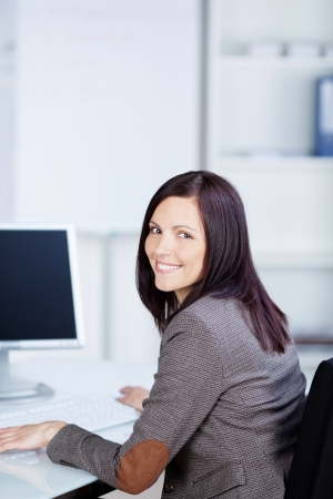 Charming businesswoman working in front of her computer photo