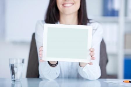 Donna sorridente che mostra un tablet contro lo sfondo sfocato Archivio Fotografico - 21146865