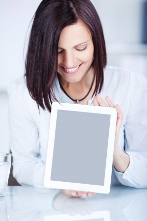 Smiling brunette woman presents her ipad touch in a close up shot photo