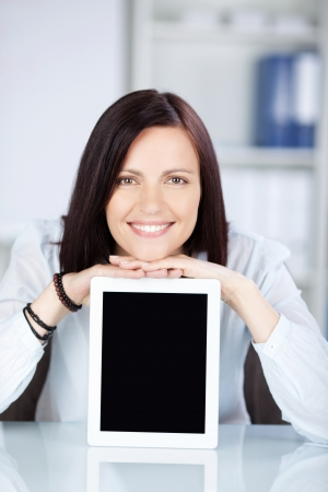 frontal view: Smiling beautiful female laying her chin on ipad touch