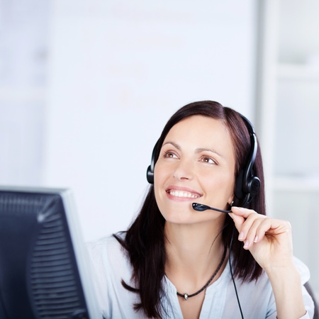 customer service representative: Call center operator with headphone looking at something Stock Photo