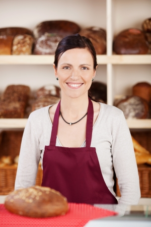 Smiling woman in apron with big bread on the table photo