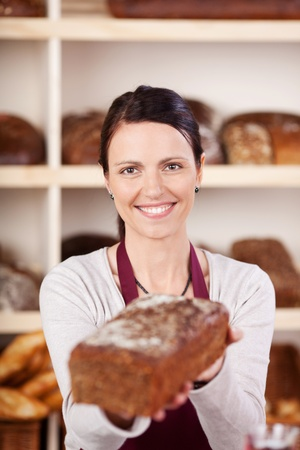 Smiling bakery worker holding out a gourmet loaf of bread in her hands offering it to the viewer, focus to her face photo