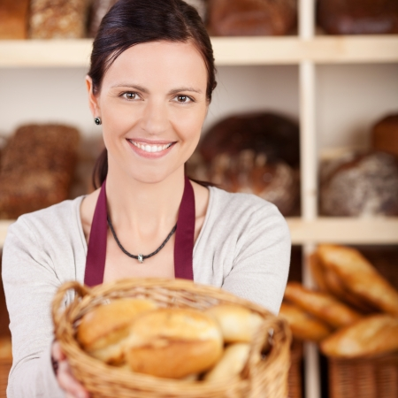 Beautiful female bakery worker with a charming friendly smile offering a basket of assorted bread to the viewer photo