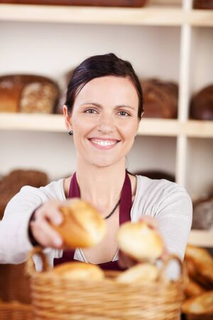 saleslady: Happy attractive female bakery worker selling fresh rolls selecting them from a basket for a customer, focus to her face Stock Photo