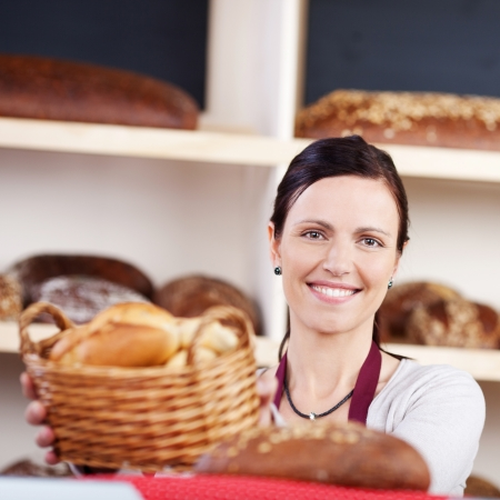 saleslady: Beautiful smiling woman working in a bakery with a basket of fresh rolls in her hands looking at the camera, focus to her face Stock Photo