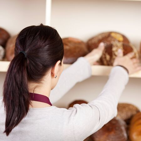 saleslady: Portrait of woman holding bread in a rear view shot