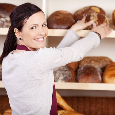 saleslady: Friendly female bakery employee looking back over her shoulder and smiling as she reaches for a loaf bread on a shelf
