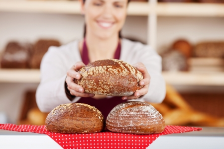 wholemeal: Delicious fresh crusty loaves of bread on a bakery counter with a female assistant holding one in her hands