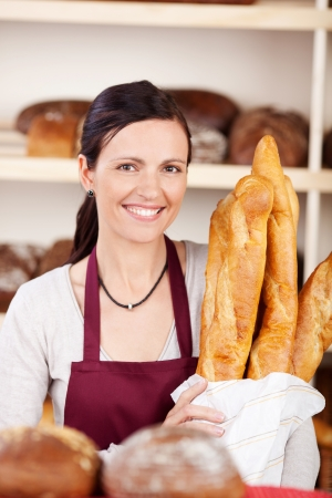french bakery: Smiling woman working in a bakery holding a packet full of long crisp crusty golden baguettes in her hands
