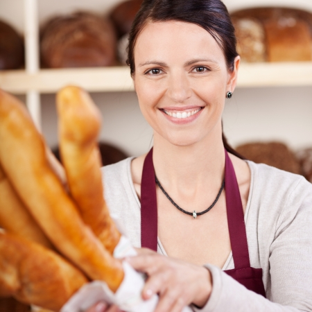 selling service smile: Smiling saleslady in a bakery holding a large white paper packet of freshly baked crusty baguettes in her arms