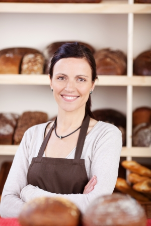 saleslady: Attractive young female owner of a bakery standing with folded arms looking at the camera with a confident smile