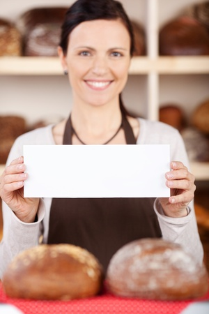 saleslady: Attractive friendly bakery assistant holding a small blank sign in her hands as she stands in front of shelves packed with fresh loaves of bread