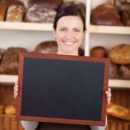 bakery store: Beautiful smiling young bakery worker holding a blank chalkboard, blackboard or slate in her hands with copyspace for text